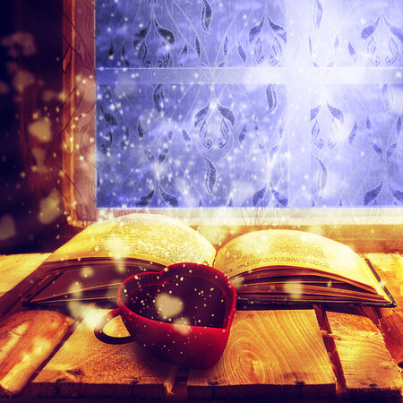Open old book of magic with cup of coffee photo