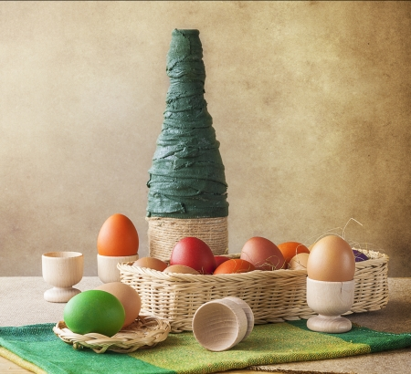 Still life. Colorful Easter eggs with basket and vase photo