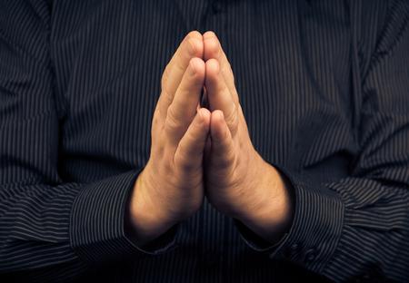Closeup of praying white man in dark shirt photo
