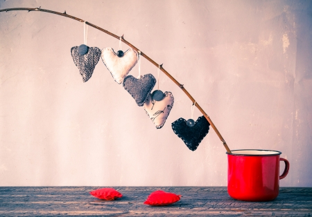 Heart hanging on a twig in a red cup Фото со стока