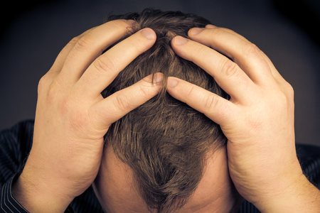 brooding: A depressed man with his hands over his face Stock Photo