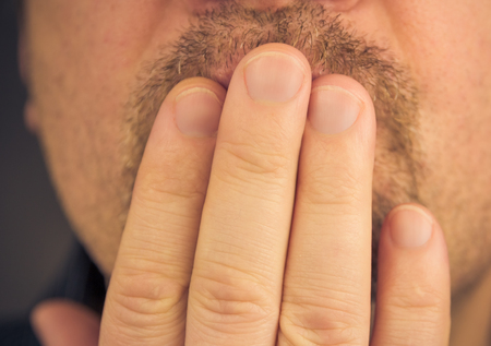 Man covering mouth with hand, not laughing or in silence photo