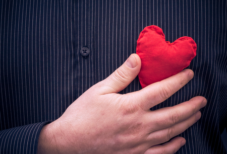 Closeup of a red heart in the hand of a man photo