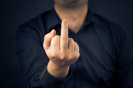 offensive: Man in shirt is showing fuck off with the middle finger Stock Photo