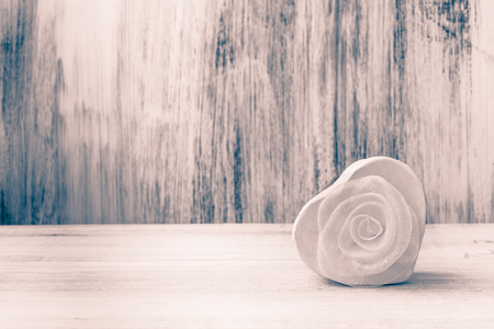 white backing: White heart with rose on white wooden background Stock Photo