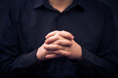 A man wearing a shirt with folded hands photo