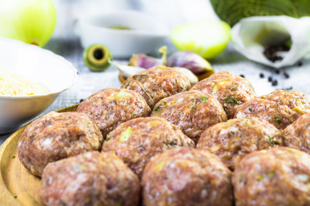 Raw meat balls of minced beef prepared for roll in breadcrumbs photo