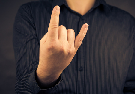 A mans hand giving the Rock and Roll sign photo