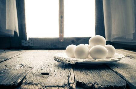 White egg on the kitchen table in a rural hut photo