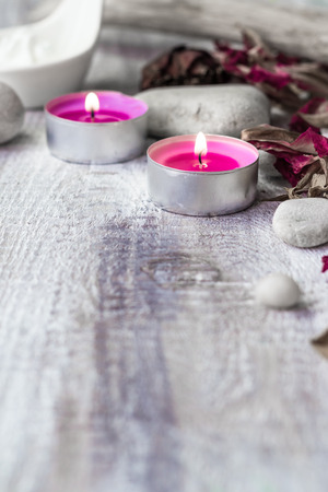 Stones, candles and petals of the rose on wooden background Stock Photo