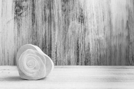 White heart with rose on white wooden background photo
