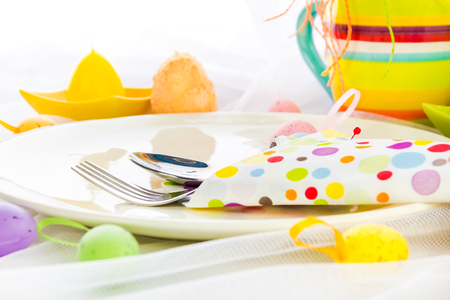 Cutlery wrapped in a napkin on Easter table photo