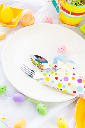 Easter table setting with silverware wrapped in a napkin photo