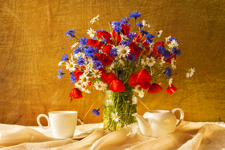 Still life with a bouquet of camomiles, cornflowers and poppies