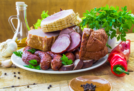 A plate of various kinds of sausages surrounded by greens photo