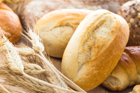 Different bakery products among the ears of cereals Фото со стока