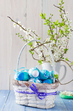 Easter eggs in a basket and spring branches photo