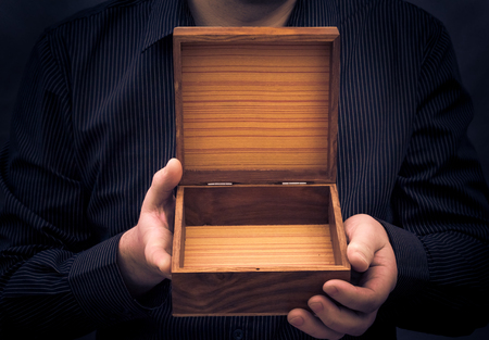 An empty casket in the hands of a man photo