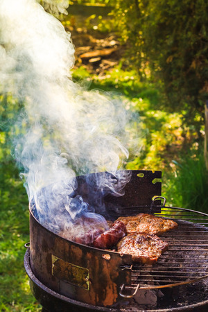 Barbecue in the garden. Process of cooking meat on grill