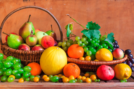 Wooden table full of fresh fruit in baskets photo