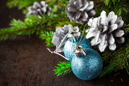 backing: Christmas spruce branches, pine cones and Christmas balls on a wooden background