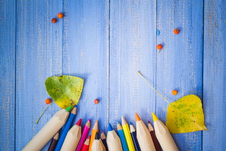 Vintage background: colored pencils and autumn fruits on a blue table photo