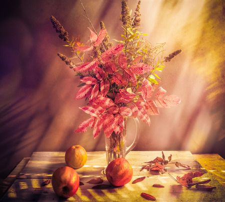Fall bouquet: Still Life with autumnal sprigs and apples photo