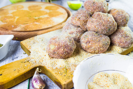 Raw meat balls of minced beef with rolled in breadcrumbs photo