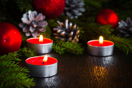 Christmas spruce branches and lighted candles on a wooden  photo