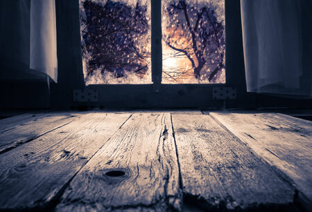 Old rural interior: a window table overlooking the winter evening photo