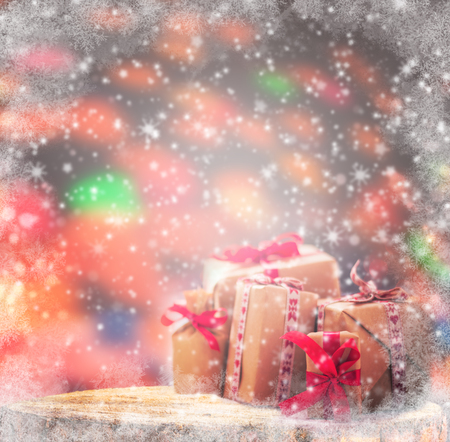 white backing: Winter background: wrapped gifts on a wooden trunk. Its snowing