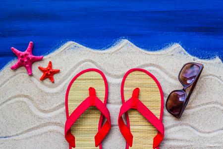 flip flops: Sea shells and flip flops on beach sand