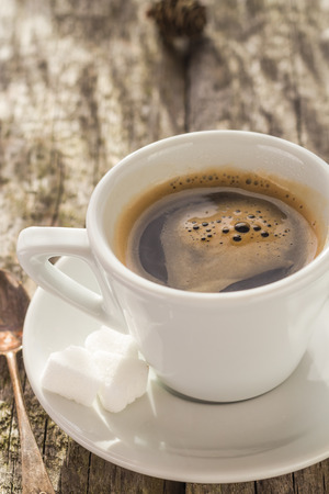 expresso: Cup of black coffee on wooden board and pines Stock Photo