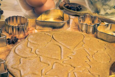 biscuit dough: Christmas glazed biscuit shapes imprinted in the dough. Kitchen table with ingredients