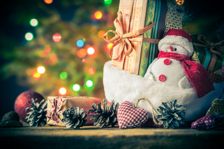 christmas grounds: Christmas card: Snowman of ornaments and gifts with a tree with lights in the background