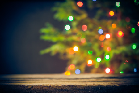 christmas tree ornaments: Festive background: wooden table and Christmas tree with lights