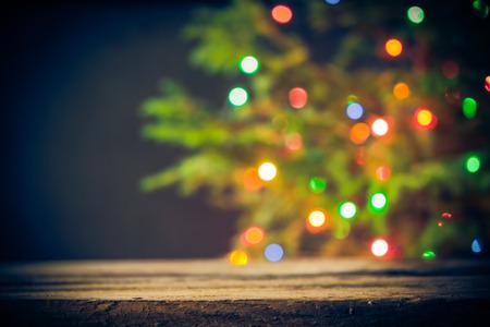 Festliche Hintergrund: Holztisch und Weihnachtsbaum mit Lichtern