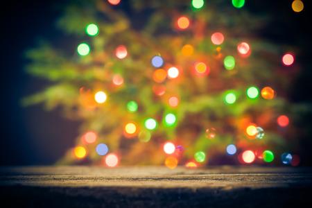 Fundo festivo: mesa de madeira e árvore de Natal com luzes Banco de Imagens