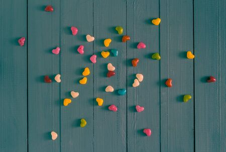 felling: Many colorful little hearts on the wooden background