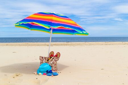 sunshade: Sunshade with a bag of sunbathers on the beach. Stock Photo