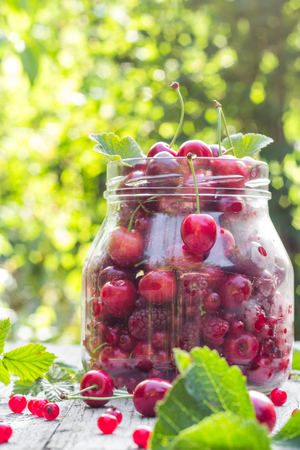 pickling: Glass jar full of fruits cherries and raspberries