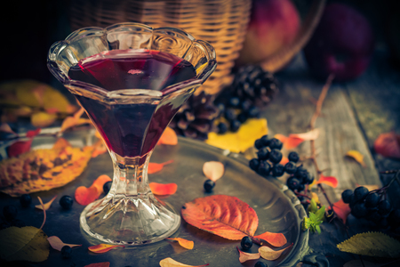 tincture: Fall in the kitchen: the cup with a tincture of chokeberry on a wooden table