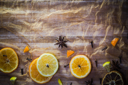 Citrus and spices: colorful  with slices of lemon, orange, cloves and cinnamon Standard-Bild