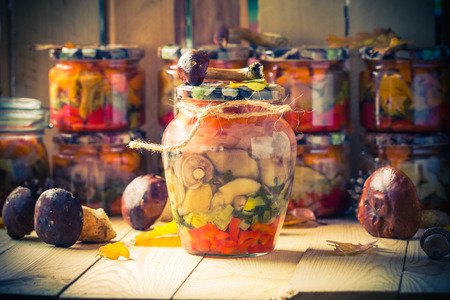 Autumn harvest. Mushrooms marinated with vegetables in jars