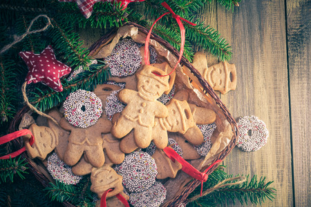 Christmas table: basket with gingerbreads. Sweets and sprigs of spruce. Place for text