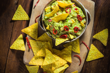 Bowl of guacamole with corn chips on a wooden table