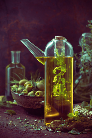 A bottle with olive oil and fruits and branches of herbs