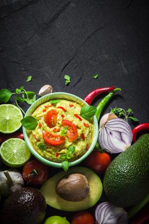 Guacamole and ingredients: tomato, chilli pepper, lime, onion, garlic, dill and oregano