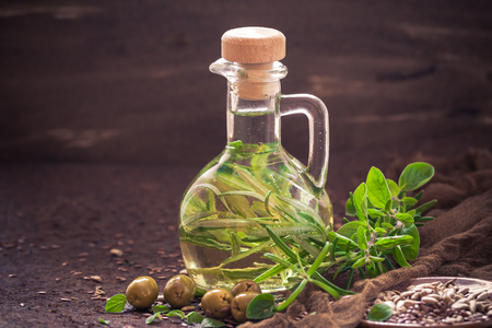 A bottle filled with olive oil with the addition of sprigs of a rosemary branch