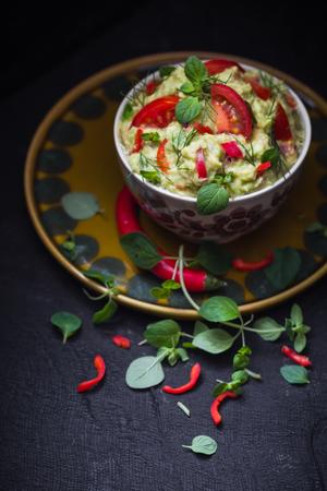 A bowl of guacamole with tomato, chilli pepper, lime, onion, garlic, dill and oregano